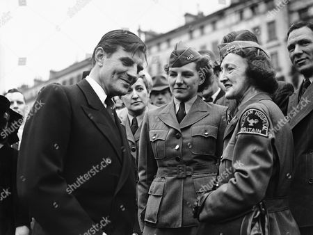 In celebration of independence Day, John Winant, American ambassador to Britain, gave a garden party reception at the American Embassy in London,, which was used for the first time since the war for this occasion. Ambassador Winant chats to American nurses, Helen Couch, and Helen MacDonald, who were invited to the garden party reception
