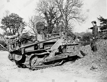 American troops with the AEF in Northern Ireland, are hard at work developing their campsites. Clearing the ground with a bulldozer are: Corporal Anneus Nelson of Middle River, Minn., and Private Loyal Albertson of Twin Valley, Minn. Left to right on machine. Directing operations is Corporal. Arthur Meyer of Cleveland, O