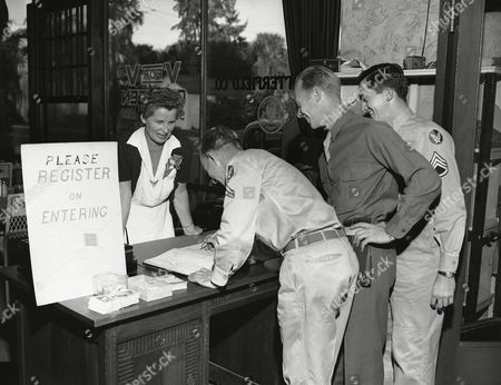 Palm beach, Florida's showplace for the elite, is a busy spot this winter. Society folks are flocking to the resort, are doing war work and going places. Here at the volunteers for victory canteen, socialite Mrs. Florence M. Howell of Devon, Pa., the canteen's registrar, helps three servicemen register, . They are left to right: corpiearl black of Cincinnati, Pfc. Jimmy Evers of Chicago, Ill. and S/Sgt. Ed Ternane of Philadelphia, PA