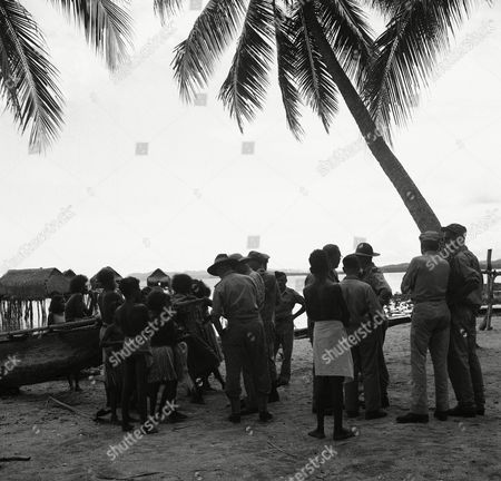 """Young and old, boys and girls, approached with multi-colored single shells, strings of shells and seeds all with the offer, """"two bob, friend,"""" on the beach of New Guinea on"""