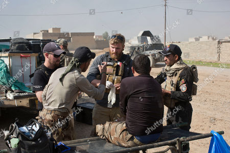 Pete Reed, center, talks to Iraqi special forces soldiers at a field clinic in Gogjali, on the eastern outskirts of Mosul, Iraq. As Iraqi forces struggle to secure recent gains against the Islamic State group in Mosul, casualties are spiking. Iraqi officers say they expect the toll among both civilians and troops to rise as the troops continue to push into the IS-held city center. At the field hospital on Mosul's eastern outskirts, teams of Iraqi and Western volunteer medics are treating a family badly burned by a car bomb, children maimed by booby-trapped explosives and soldiers suffering from shrapnel and gunshot wounds