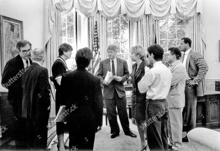 United States President Bill Clinton meets with Attorney General Janet Reno in the Oval Office. White House Counsel Vince Foster, far left, is whispering into the ear of fellow counsel Bernard Nussbaum.  Press Secretary Dee Dee Myers is at the immediate right of The President.