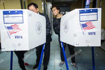 Nancy Liu, right, watches her husband John Liu, center, as he is helped by a Chinese translator, left, at a polling station in Flushing, the Queens borough of New York, . Born in Taiwan, John and Nancy immigrated to the United States 38 years ago, and this is their first time voting