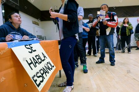 """A sign that reads """"Spanish is Spoken Here"""" hangs as voters check in at the North Hollywood Amelia Earhart Regional Library polling station in Los Angeles on"""