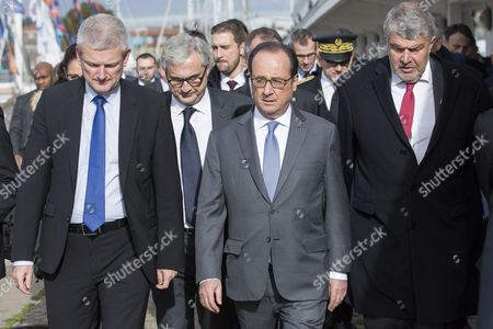 French President Francois Hollande (C) walks with La Rochelle's mayor Jean-Francois Fountaine (R) and MP Olivier Falorni (L)