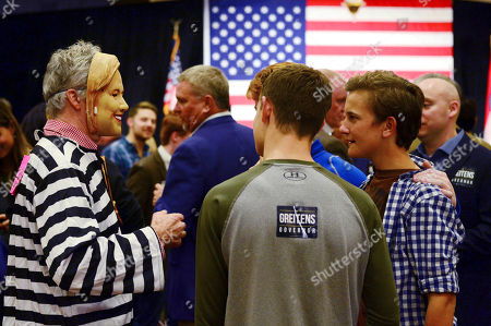 Joe Dubuque, left, wears a costume of Democratic presidential candidate Hillary Clinton in a prison jumpsuit as he talks with supporters of Missouri Republican gubernatorial candidate Eric Greitens during an election night watch party, in Chesterfield, Mo