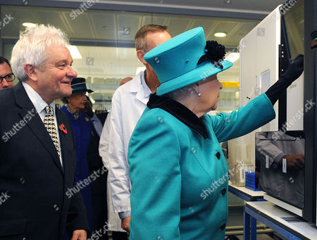 Paul Nurse Director of the Francis Crick Institute watches as Queen Elizabeth II pushes a button to start sequencing Sir Paul's genome during a visit to officially open the Francis Crick Institute