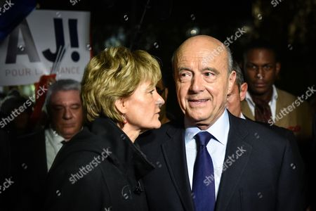 Stock Image of Alain Juppe salutes supporters as he leaves his campaign rally with his wife Isabelle Legrand-Bodin in Bordeaux