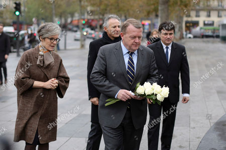 Danish ambassador to France, Kirsten Malling Biering, left, Danish Prime Minister Lars Lokke Rasmussen, center, and French columnist for Charlie Hebdo newspaper Patrick Pelloux, right, pay their respects to the victims of the 2015 Paris attacks, in Paris