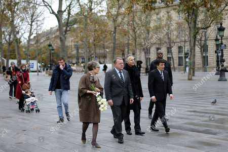Danish ambassador to France, Kirsten Malling Biering, center left, Danish Prime Minister Lars Lokke Rasmussen, center, and French columnist for Charlie Hebdo newspaper Patrick Pelloux, right, arrive to lay flowers to the victims of the 2015 Paris attacks, in Paris