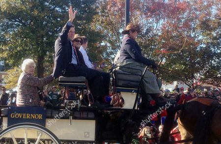 Democratic Gov.-elect John Carney Jr. waves to the crowd as he shares a carriage ride with his wife, Tracey, and Republican opponent state Sen. Colin Bonini during the Return Day celebration, in Georgetown, Del. The post-election ritual, which includes a symbolic burying of a hatchet, offers politicians of all stripes an opportunity to put aside their partisan differences, if only for a moment. AP Photo by Randall Chase