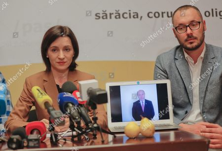 "Stock Image of Moldovan presidential candidate Maia Sandu, left, sits as a statement by former Romanian president Traian Basescu runs on a computer screen during a press conference in Chisinau, Moldova, . Moldovans will directly elect their president on Sunday for the first time in 20 years. Banner reads ""I chose to defeat poverty, corruption, the oligarchs"