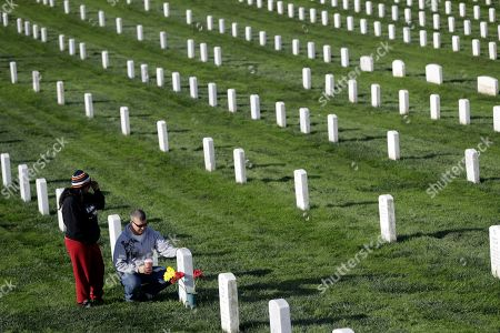 Stock Photo of Mark Moseley, Denise Moseley Mark Moseley, bottom, and his wife Denise, of Half Moon Bay, Calif., place flowers on the grave of Mark's father James Moseley, a Korean war veteran, on veterans day at Golden Gate National Cemetery, in San Bruno, Calif