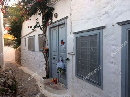 """Flowers and a candle lie outside the house of Leonard Cohen on the Greek island of Hydra, southwest of Athens, . Cohen the baritone-voiced Canadian singer-songwriter who seamlessly blended spirituality and sexuality in songs like """"Hallelujah,"""" ''Suzanne"""" and """"Bird on a Wire,"""" has died at age 82 at his home in Los Angeles, his son said"""