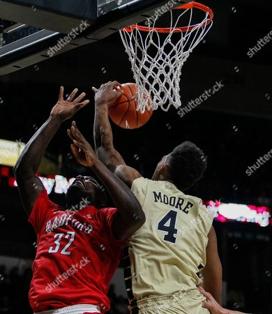 Doral Moore (4) of the Wake Forest Demon Deacons blocks the shot from Randy Phillips (32) of the Radford Highlanders in the NCAA Basketball matchup between the Radford Highlanders and the Wake Forest Demon Deacons at LJVM Coliseum in Winston-Salem, NC