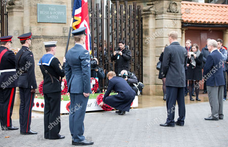 Prince Harry lays a wreath for remembrance day at the Rose and Poppy Gates before the match RFU President Peter Baines (R) with Lewis Moody
