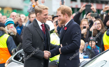 Lewis Moody (L) greets Prince Harry (R) as they lay a wreath for remembrance day at the Rose and Poppy Gates before the match