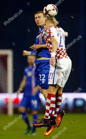 Iceland's Eidur Gudjohnsen, left, is airborne with Croatia's Domagoj Vida during the World Cup Group I qualifying soccer match between Croatia and Iceland, at Maksimir stadium in Zagreb, Croatia
