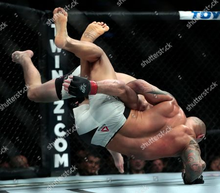 Thiago Alves, bottom, is dropped by Jim Miller during a catchweight mixed martial arts bout at UFC 205, at Madison Square Garden in New York