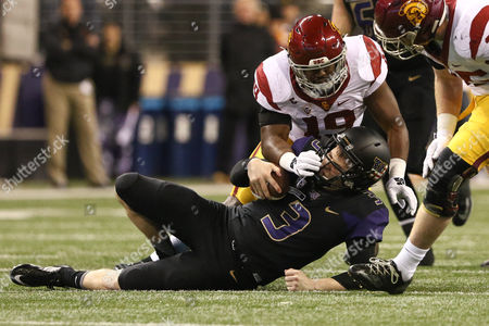 Washington's quarterback Jake Browning (3) is hit by Southern California's linebacker Michael Hutchings (19) after sliding during a game between the USC Trojans and the Washington Huskies at Husky Stadium in Seattle, WA on , 2016. Southern California won 26-13