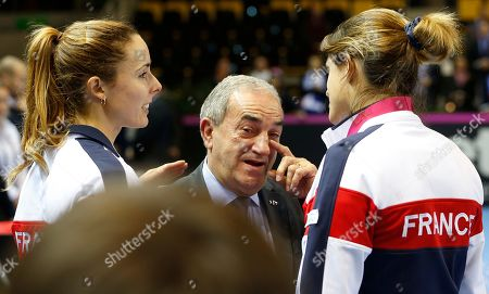 Jean Gachassin, center, wipes a tear with French player Alize Cornet, left, and team captain Amelie Mauresmo after their loss in the Fed Cup final in Strasbourg, eastern France, . Czech Republic retains Fed Cup title by beating France 3-2