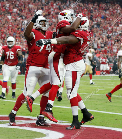 Arizona Cardinals running back David Johnson, center, celebrates his touchdown with D.J. Humphries (74) and Arizona Earl Watford (78) during the first half of an NFL football game against the San Francisco 49ers, in Glendale, Ariz
