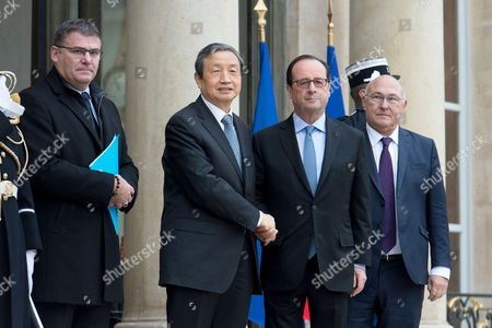 French President Francois Hollande (2ndR) welcomes Chinese Vice Premier Ma Kai (2ndL), next to French Finance Minister Michel Sapin (R) and French Minister of State for the Industry Christophe Sirugue (L), upon his arrival at the Elysee Presidential palace in Paris