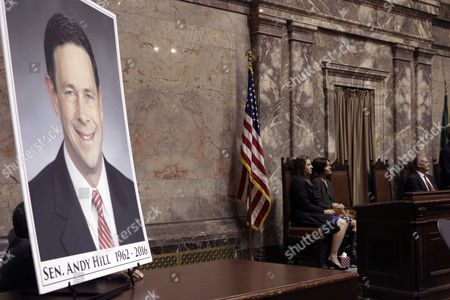 A photo of the late Republican Sen. Andy Hill is displayed in the Senate chambers as his daughter Katie, left, and widow Molly sit nearby during a memorial at the Legislature, in Olympia, Wash. Hill died of lung cancer on Oct. 31