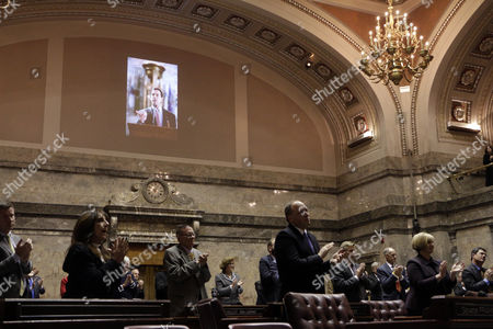 House and Senate lawmakers applaud in the Senate chambers after hearing from Molly Hill, widow of the late Republican Sen. Andy Hill, during a memorial at the Legislature, in Olympia, Wash. Sen. Hill died of lung cancer on Oct. 31