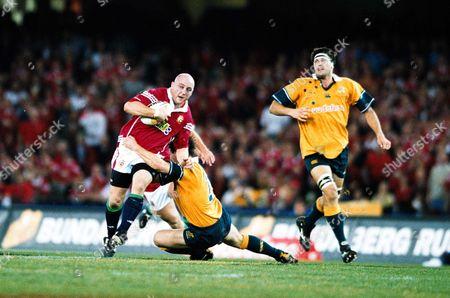 Keith Wood (British Lions) tackled by Matt Burke (Australia) as John Eales looks on Australia v British Lions 2nd Test Colonial Stadium Melbourne Victoria 7/07/2001 Australia Melbourne