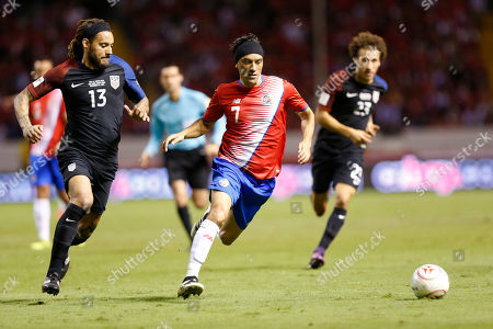 Costa Rica's Christian Bolanos, center, dribbles the ball pst United States' Jermaine Jones, left, during a 2018 World Cup qualifying soccer match in San Jose, Costa Rica