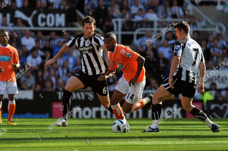 Football - Barclays Premier League - Newcastle United vs Blackpool Elliot Grandin (Blackpool) weaves his way past Joey Barton (Newcastle United) and Mike Williamson (Newcastle United) at St James' Park