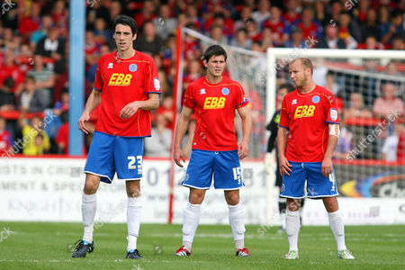 Stock Photo of Football - League Two - Aldershot Town vs Crawley Town From left to right Aldershots Peter Vincenti Aaron Morris and Luke Guttridge during a brake in play at the EBB Stadium