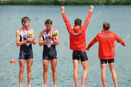 Rowing - 2012 London Olympics - Men's Lightweight Double Sculls Medal Ceremony Great Britain's silver medalists Mark Hunter and Zac Purchase look on the as the gold-winning Danes celebrate at Eton Dorney