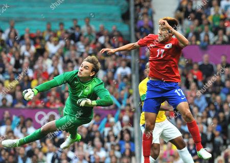Football - 2012 London Olympics - Semi-Final: South Korea 0 Brazil 3 Brazil goalkeeper Gabriel Vasconcelos Ferreira saves under pressure from Korea's Hyunsung Kim at Old Trafford