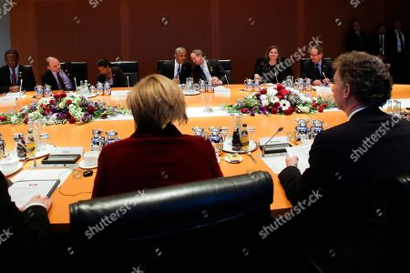 U.S. President Barack Obama, background center left, talks to US ambassador in Germany John B. Emerson prior to a bilateral meeting with German Chancellor Angele Merkel, foreground left, at the chancellery in Berlin