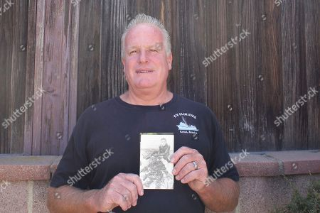 """Tim Bridger holds a photo of his younger brother, Michael, in Redondo Beach, Calif. Michael was a skilled diver and worked in and around the water most of life. Michael Bridger died on Sept. 21, 2012, after suffering a heart attack while cleaning a 24-foot tank being prepared for a scene in the film """"The Lone Ranger."""" Safety inspectors fined the film's producers more than $61,000 for violating several safety protocols, including allowing a backup diver to leave Bridger in the water for 10 minutes, not having anyone with adequate CPR training on site, and not requiring health exams for divers being used on the film"""