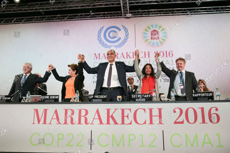 """U.N. climate chief Patricia Espinosa, 2nd left, and Morocco's Foreign Minister Salaheddine Mezouar, centre, celebrate after the proclamation of Marrakech, at the COP22 climate change conference, in Marrakech, Morocco, . Governments meeting for U.N. climate talks have reiterated their commitment to the Paris Agreement with a proclamation saying climate action is """"irreversible,"""" the buzzword at the two-week conference after the uncertainty caused by the U.S. election"""
