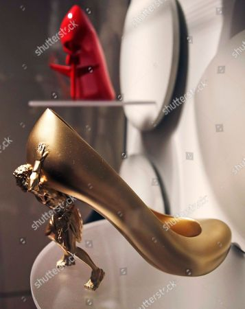 """Stock Picture of A high heel shoe titled """"The Gold Digger"""" by designer Sebastian Errazuriz, featuring a figure holding up the upper portion, is displayed at the Peabody Essex Museum in Salem, Mass., From flats to stilettos, what we put on our feet says something about who we are. That's the premise of new exhibition in Massachusetts. """"Shoes: Pleasure and Pain"""" opens Saturday, Nov. 19, 2016, at the Peabody Essex Museum in Salem"""