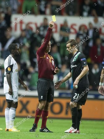 Stock Image of Football - 2013 / 2014 Europa League - Group A: Swansea City vs St Gallen referee duarte gomes holds up a yellow card for ivan martic at the Liberty Stadium  UK swansea