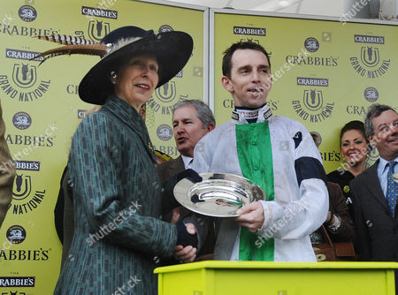 Horse Racing - 2014 Aintree Grand National Meeting - Grand National Day Jockey Leighton Aspell is presented his winning Jockeys Plate by HRH Princess Anne after Pineau de Re's victory in the Crabbies Grand National Dr Richard Newland ( trainer ) right