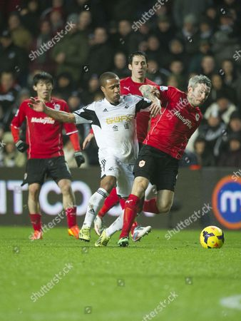 Football - 2013 / 2014 Premier League - Swansea City vs Cardiff City Wayne Routledge of Swansea tackles Kevin Mcnaughton in the South Wales derby match at the Liberty Stadium  UK swansea