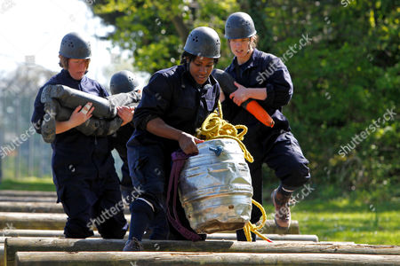 Rugby Union - England Women Media Day - HMS Collingwood Maggie Alphonsi carries a beer barrel and her team mates carry a life size dummy whilst completing the Royal Navy assault course at HMS Collingwood