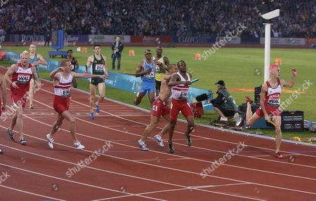 Stock Photo of Athletics - 2002 Manchester Commonwealth Games - Men's 4x400m Relay Final England's Sean Baldock is joined by team-mates as he crosses the line to win the gold medal at the City of Manchester Stadium Wales' Matthew Elias right wins the silver