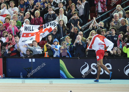 Athletics - 2014 Glasgow Commonwealth Games - Day Six Men's 110m Hurdles Final England's William Sharman goes over to the crowd to celebrate during his lap of honour after winning the silver medal at Hampden Park