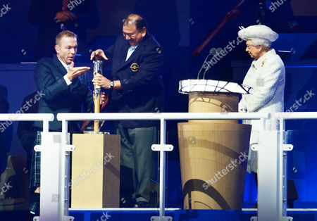 2014 Glasgow Commonwealth Games - Opening Ceremony Ex-cyclist Sir Chris Hoy helps President of the Commonwealth Games Federation HRH Prince Imran open the baton with its message as Queen Elizabeth II waits at Celtic Park Scotland Glasgow