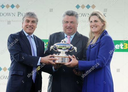 Horse Racing - 2015 bet365 Jump Finale - Sandown Park Paul Nicholls is presented the Champion trainer trophy by John Inverdale and Tina Cook