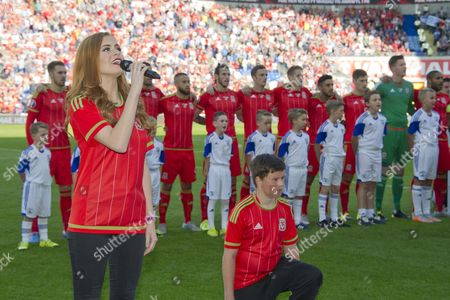 Football - 2015 / 2016 European Qualifier - Group B: Wales vs Israel Sophie Evans sings the Welsh anthem before the match with Wales team singing in background at Cardiff City Stadium  UK cardiff