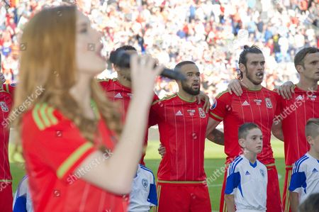 Football - 2015 / 2016 European Qualifier - Group B: Wales vs Israel Sophie Evans out of depth of field sings the Welsh anthem before the match with Gareth Bale of Wales team singing in background at Cardiff City Stadium  UK cardiff