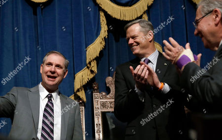 Supreme Judicial Court justice David Lowy, left, receives applause by Massachusetts Gov. Charlie Baker, center, and House Speaker Robert DeLeo, right, during his installation ceremony at the Statehouse in Boston
